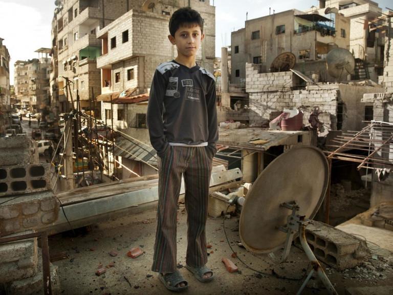 MO-ACN Foto van een jongen in een verwoeste wijk in Allepo