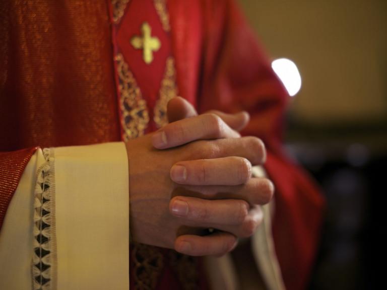 photodune-20454029-catholic-priest-on-altar-praying-during-mass-xl